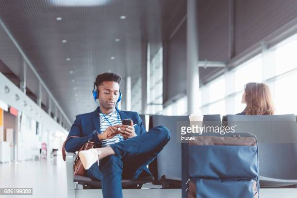 Businessman waiting at the airport lounge listening music