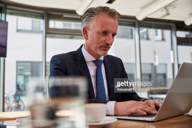 Businessman waiting at the airport, using laptop
