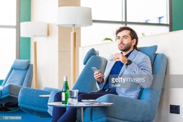 empresário à espera de voo no lounge vip do aiport - izusek - fotografias e filmes do acervo