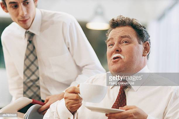 businessman waiting for manager with coffee on his lips - schamlippen stock-fotos und bilder