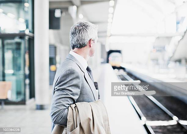 businessman waiting for train on platform - waiting stock pictures, royalty-free photos & images