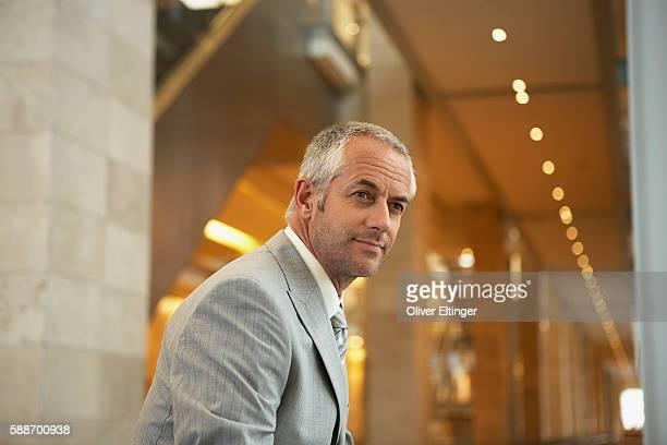 businessman waiting in corridor - oliver eltinger stock-fotos und bilder