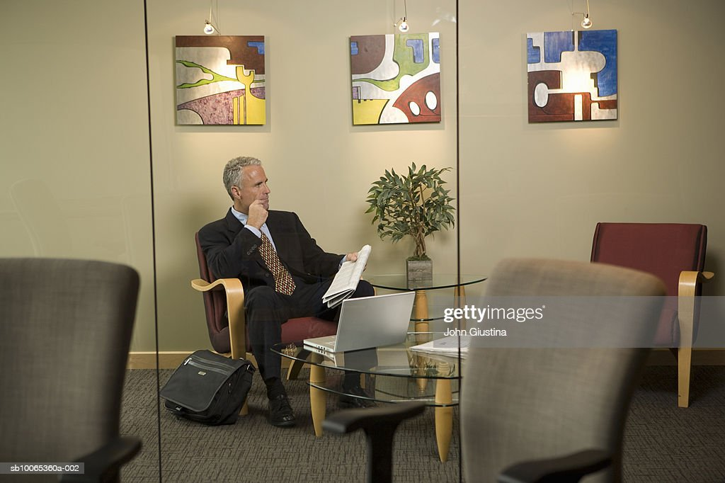 Businessman waiting in office lobby holding newspaper, looking away : Foto stock