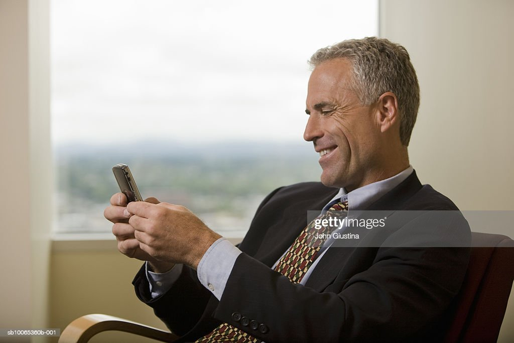 Businessman waiting in office lobby reading message, smiling : Foto stock