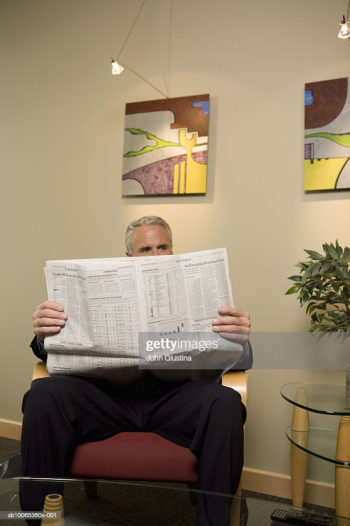 Businessman waiting in office lobby, reading newspaper : Foto stock