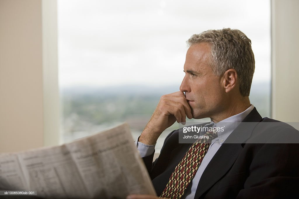 Businessman waiting in office lobby with newspaper, looking away : Foto stock