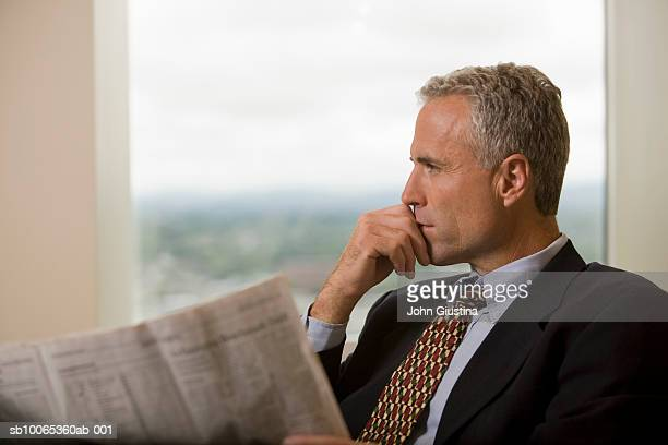 Businessman waiting in office lobby with newspaper, looking away