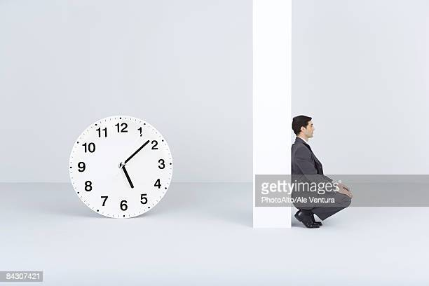 Businessman waiting, near oversized clock