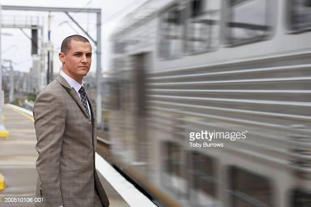 Businessman waiting on station platform, portrait (blurred motion)
