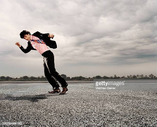 Businessman walking against strong wind