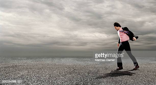 Businessman walking against wind, outdoors, side view