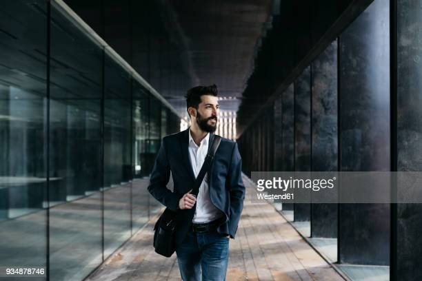 businessman walking along arcade - white jacket stock photos and pictures