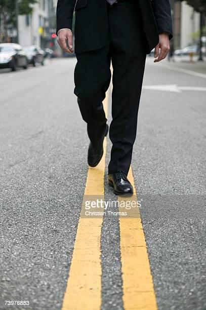 Businessman walking along dividing line on a city street