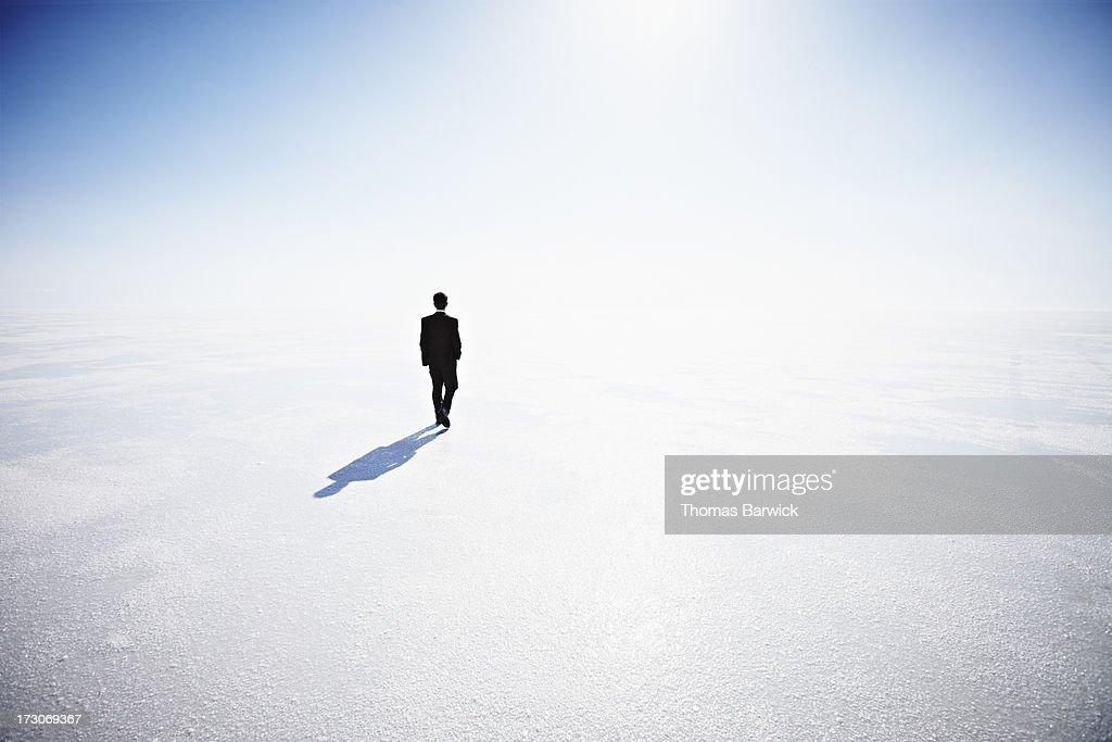 businessman walking along empty landscape ストックフォト getty images