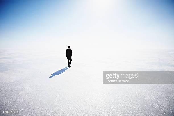 Businessman walking along empty landscape