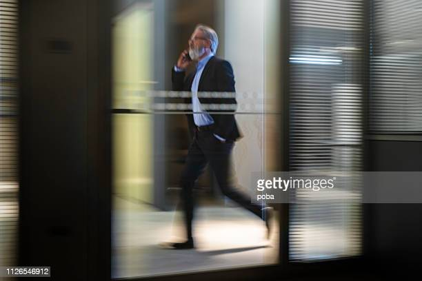businessman  walking along office  walkway - business finance and industry stock pictures, royalty-free photos & images