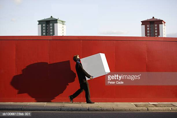 Businessman walking along red wall, carrying box, side view