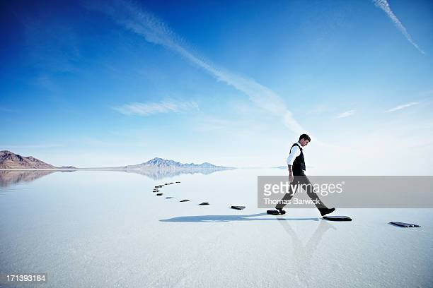 Businessman walking along stone path in lake