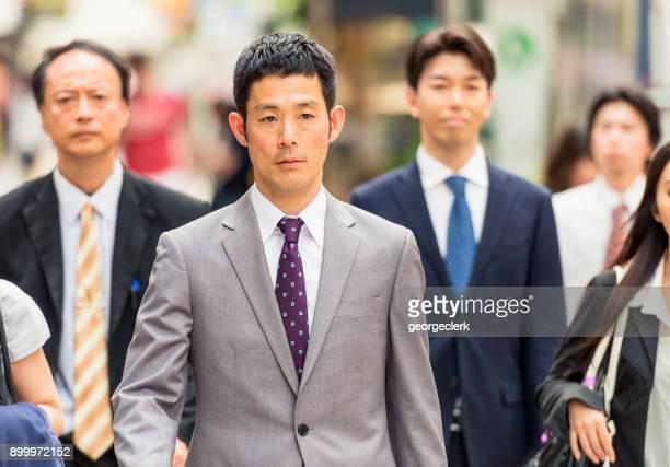 zakenman wandelen onder pendelaars. - spitsperiode stockfoto's en -beelden