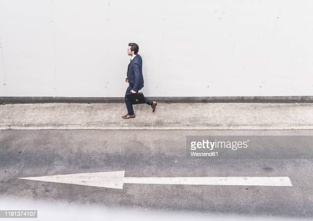 businessman walking at road with arrow sign - following arrows stock pictures, royalty-free photos & images