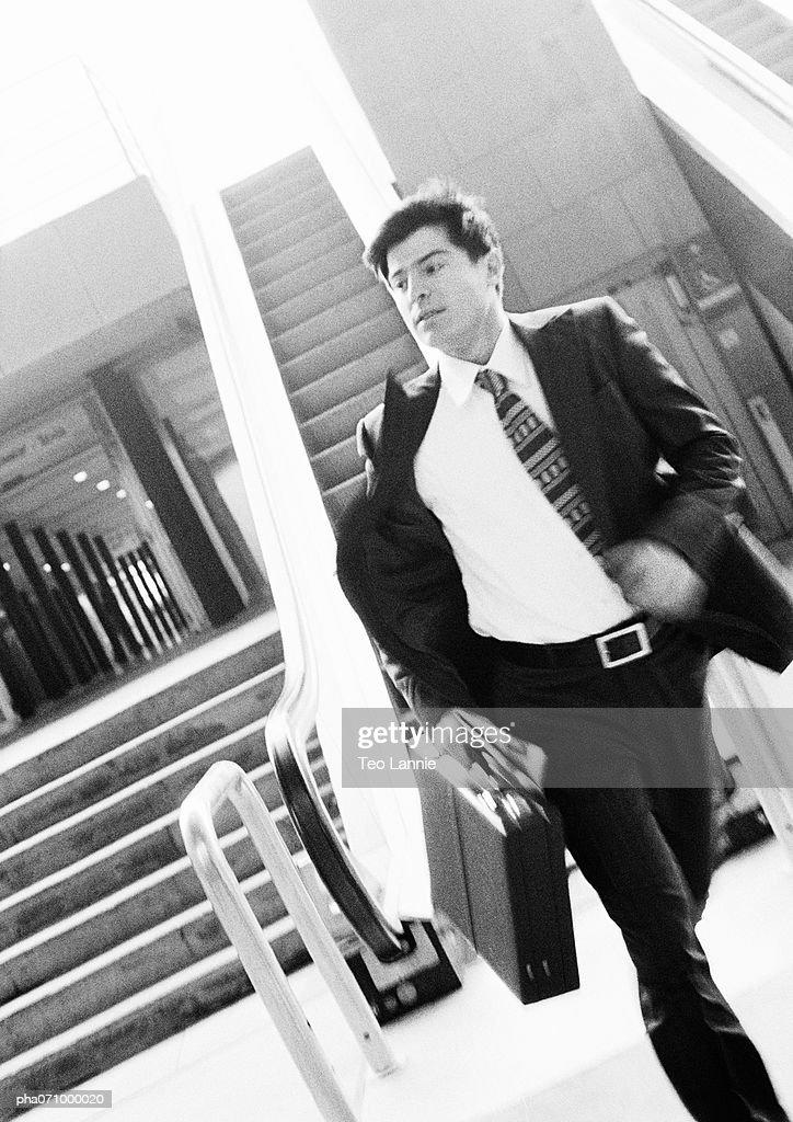 Businessman walking away from escalator, holding briefcase, blurred motion, b&w. : Stockfoto