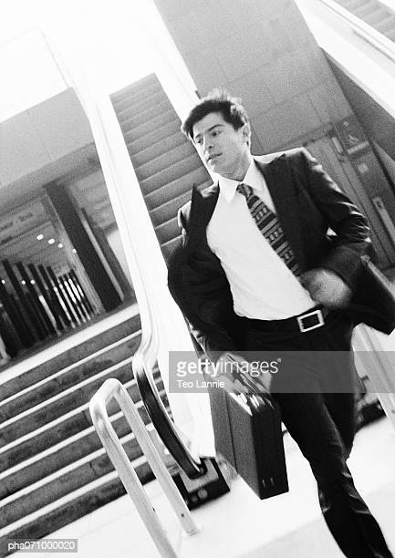 Businessman walking away from escalator, holding briefcase, blurred motion, b&w.