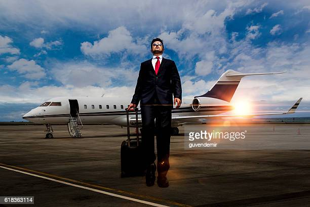Businessman walking away from private jet after flight