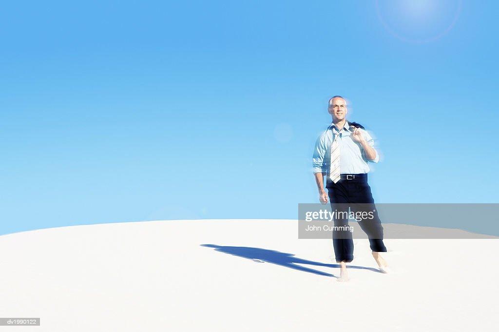 Businessman Walking Barefoot in a Desert : Stock Photo