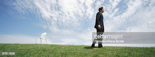 businessman walking barefoot in grassy field, empty chair nearby - costume complet photos et images de collection