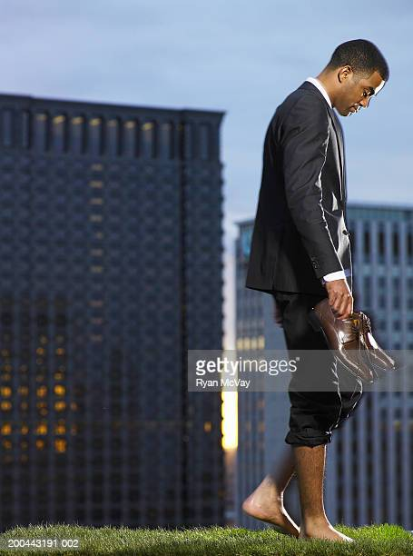 businessman walking barefoot in park - hairy legs stock photos and pictures