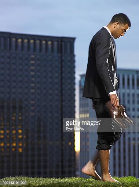 Businessman walking barefoot in park