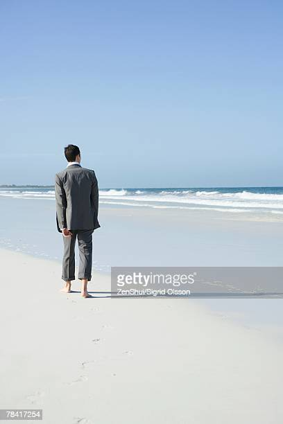 businessman walking barefoot on beach, rear view - rolled up trousers stock pictures, royalty-free photos & images