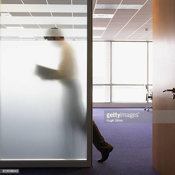 Businessman Walking Behind Glass Wall