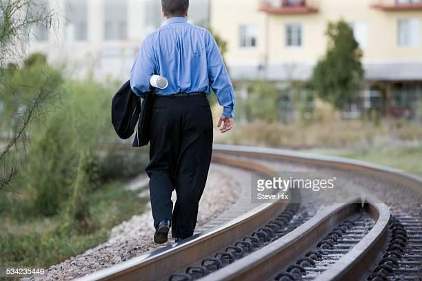 Businessman Walking Beside Railroad Tracks
