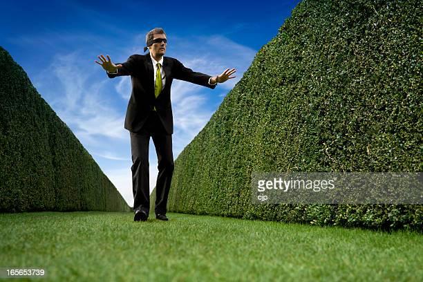 Businessman Walking Blindfolded up a Blind Alley