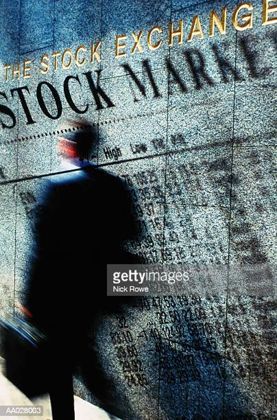 Businessman Walking by Stock Market Quotes