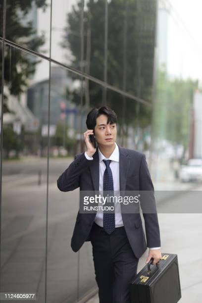 businessman walking down city street while talking on smartphone - 営業職 ストックフォトと画像
