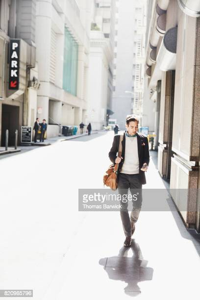 Businessman walking down city street while working on smartphone