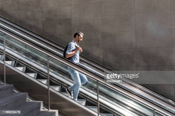 businessman walking down escalator in the city - top garment stock pictures, royalty-free photos & images