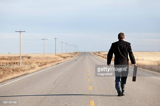 Businessman Walking Down Highway