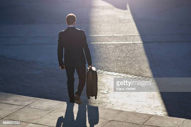 Businessman walking down staircase with suitcase