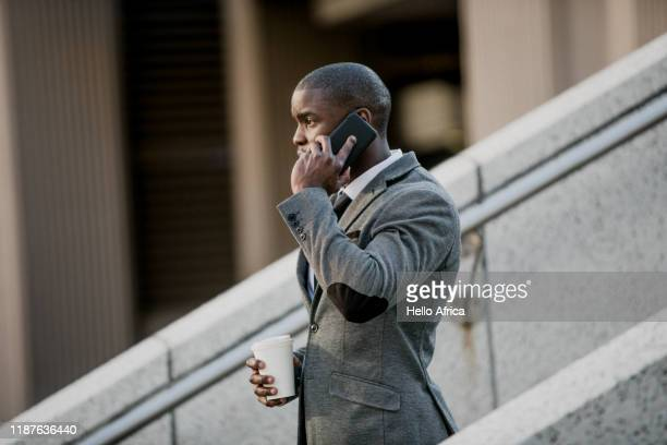 Businessman walking down stairs talking on his phone with coffee in hand
