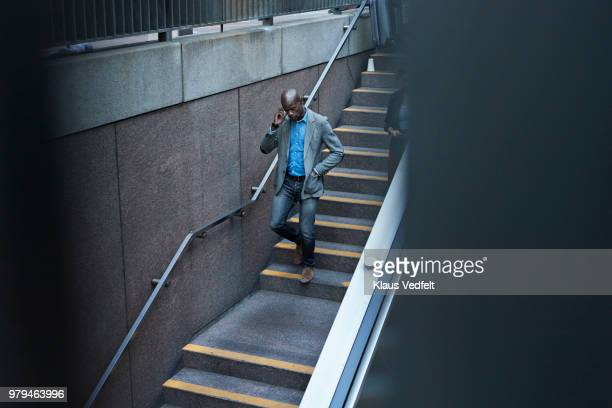 Businessman walking down stairs to metro station and talking on smartphone