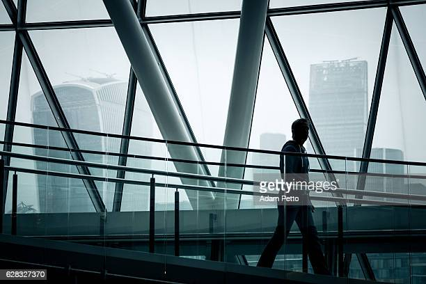 Businessman walking down stairs with London skyline in background