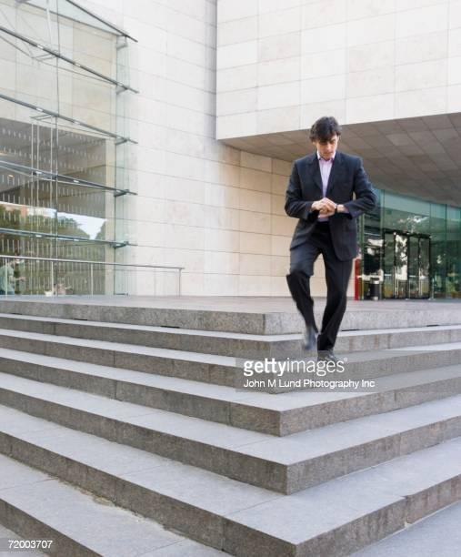 Businessman walking down steps of office building