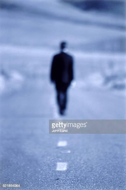 Businessman Walking Down the Road Alone