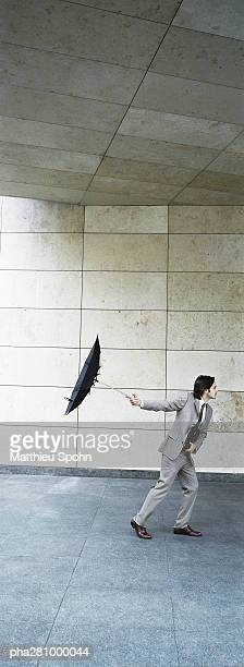 Businessman walking forward, holding umbrella inside out behind him