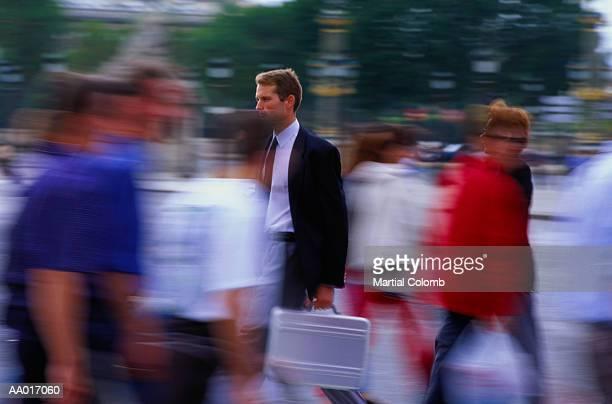 Businessman Walking in a Crowd of People