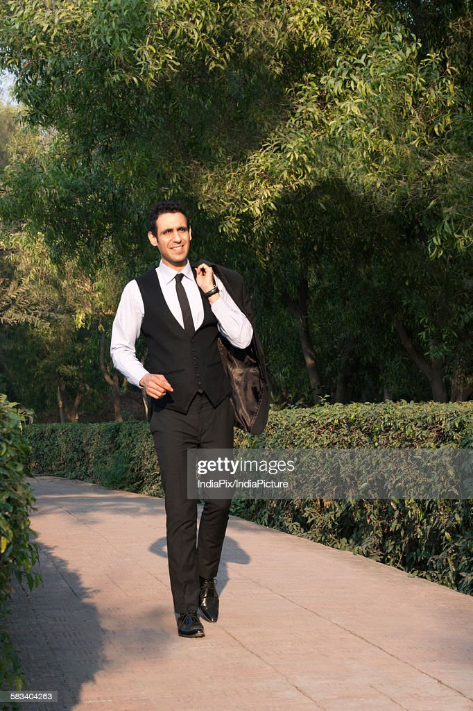 Businessman walking in a park , INDIA , DELHI : Stock Photo
