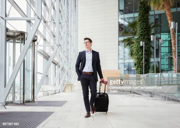 businessman walking in airport with luggage - businesswear stock pictures, royalty-free photos & images